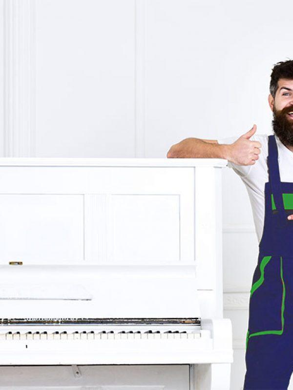 Mann mit Bart und Schnurrbart, Arbeiter in Overalls lehnen sich an Klavier, weißer Hintergrund. Loader zeigt Daumen hoch Geste. Kurier liefert Möbel bei Auszug, Umzug. Lieferservice-Konzept