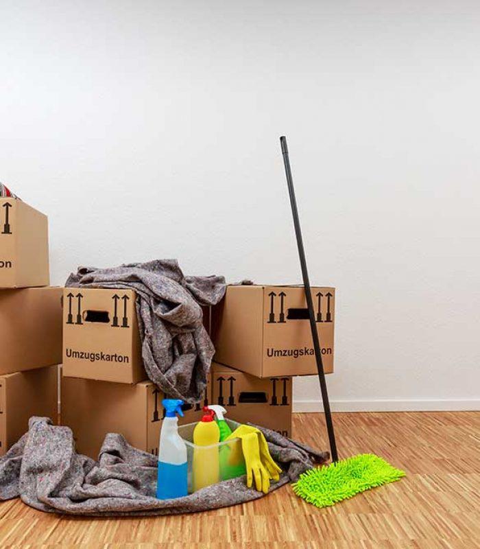 Sauberer weisser Raum mit Umzugskartons und Putzzeug