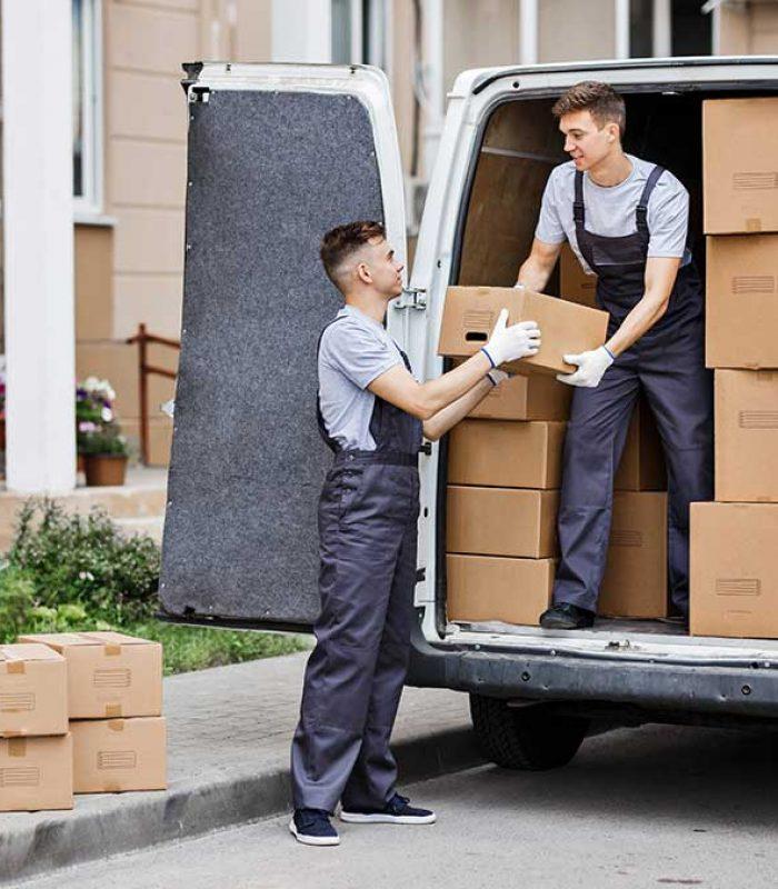Zwei Umzugshelfer in Uniform entladen den Lieferwagen